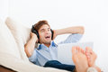 Man listening music in headphone excited sing song on the sofa with laptop at home smile relax listen to music Stock Photos