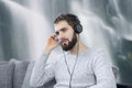 Man listening relaxation music by headset at waterfall Royalty Free Stock Photo