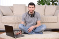 Man listening to music with earphones on laptop computer sitting on the floor near the sofa Stock Photo