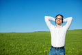 Man listening to music in a green field standing relaxing and under sunny blue sky with copyspace Royalty Free Stock Image