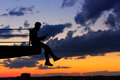 Man is listening to music on roof. Clouds and sunset