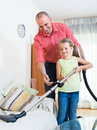 Man and little girl hoovering at home Royalty Free Stock Photo
