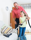 Man and little girl vacuuming at home Royalty Free Stock Photo
