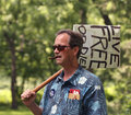 Man with live free or die sign at tea party rally in a colorful shirt sunglasses and a cigar holds a a sponsored by nebraska Stock Photos