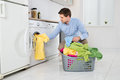 Man loading clothes into washing machine young in kitchen Royalty Free Stock Photography