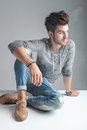 Man looking away from the camera while smoking a cigarette young fashion relaxing on floor Stock Photos