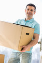 Man looking away while carrying cardboard box while entering new house Royalty Free Stock Photo