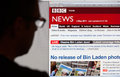 Man looking at bbc news website bath uk may a silhouetted views the latest stories on the on th may the headlines are dominated by Royalty Free Stock Images