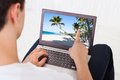 Man Looking At Beach Photo On Laptop In Living Room Royalty Free Stock Photo