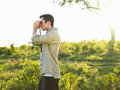 Man looking through binoculars in field side view of a Royalty Free Stock Image