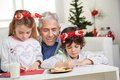 Man looking at children making christmas greeting senior men card home Stock Photo
