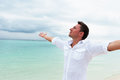 Man looking into the distance with his hands up against sea and cloudy sky Stock Photo