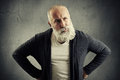 Man looking with distrust at something senior over dark grey wall Royalty Free Stock Images