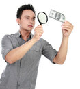 Man looking dollar bill through a magnifying glass Royalty Free Stock Photo