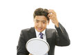 A man looking at himself in a hand mirror Royalty Free Stock Photo