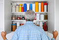 Man looking in his pantry closeup of a mature male into the cupboard is full of groceries the is seen from behind and is Royalty Free Stock Image