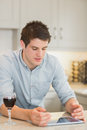 Man looking at his tablet pc with glass of red wine in kitchen Stock Photos