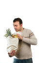 Man looking inside his grocery bag white male shopper for an item in Royalty Free Stock Image