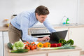 Man Looking On Laptop In Kitchen Royalty Free Stock Photo