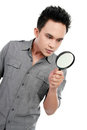 Man looking through a magnifying glass Royalty Free Stock Photography