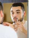 Man looking at mirror and shaving face with razor Royalty Free Stock Photo