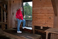 Man looking out doorway of watsons mill covered br an elderly gray haired wearing a red jacket and blue jeans is gazing through Stock Photos