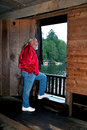 Man looking out doorway of watsons mill covered br gray haired wearing red jacket and blue jeans is gazing through window from Royalty Free Stock Photography