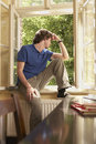 Man looking out of window sill in study room young sitting on and Royalty Free Stock Photography