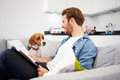 Man Looking At Paperwork And Playing With Pet Dog Royalty Free Stock Photo