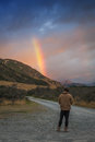 Man looking at rainbow over mountain Royalty Free Stock Photo