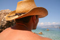 Man looking at the sea with straw hat Stock Photo