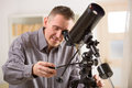 Man looking through telescope skyward astronomical standing near a window Royalty Free Stock Images