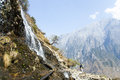 Man looking up at mountainside waterfall a hiker looks a flowing down the steeps canyon walls of tiger leaping gorge in yunnan Stock Photo