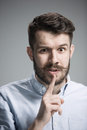 Man is looking wary over gray background wearing a blue shirt Royalty Free Stock Photo