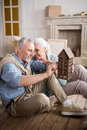 Man looking at wooden house model in hands with smiling wife Royalty Free Stock Photo