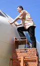 Man looks into airplane cabin a young is standing on a ladder and Stock Photography