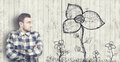 Man looks at a flower drawn on old wooden background Stock Photos