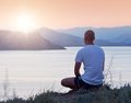 Man looks at the sunset sits on a cliff above sea and watching warm evening on coast Stock Image