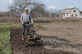 Man loosens the soil cultivator