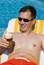 Man Lounging by the Pool with a Beer Royalty Free Stock Image