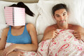 Man Lying In Bed Next To Woman Reading Book Stock Photo