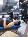 Man lying on bench in gym fitness center Royalty Free Stock Photography