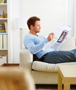 Man lying on couch reading newspaper Stock Image