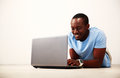 Man lying on the floor and using laptop portrait of a smiling african Royalty Free Stock Photos