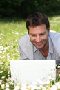 Man lying on grass with a computer Royalty Free Stock Photo