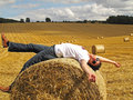 Man lying on hay bale young enjoys a in the middle of a cornfield Stock Photos