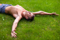 Man lying on his back on the grass a with hands sides of a side view in shorts with no shirts Stock Image