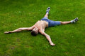 Man lying on his back on the grass a with hands sides of a side view in shorts with no shirts Stock Images