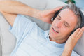 Man lying on sofa listening to music with eyes closed at home Royalty Free Stock Photo
