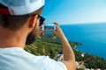 Man makes photos by a smartphone on the background of sea coast,